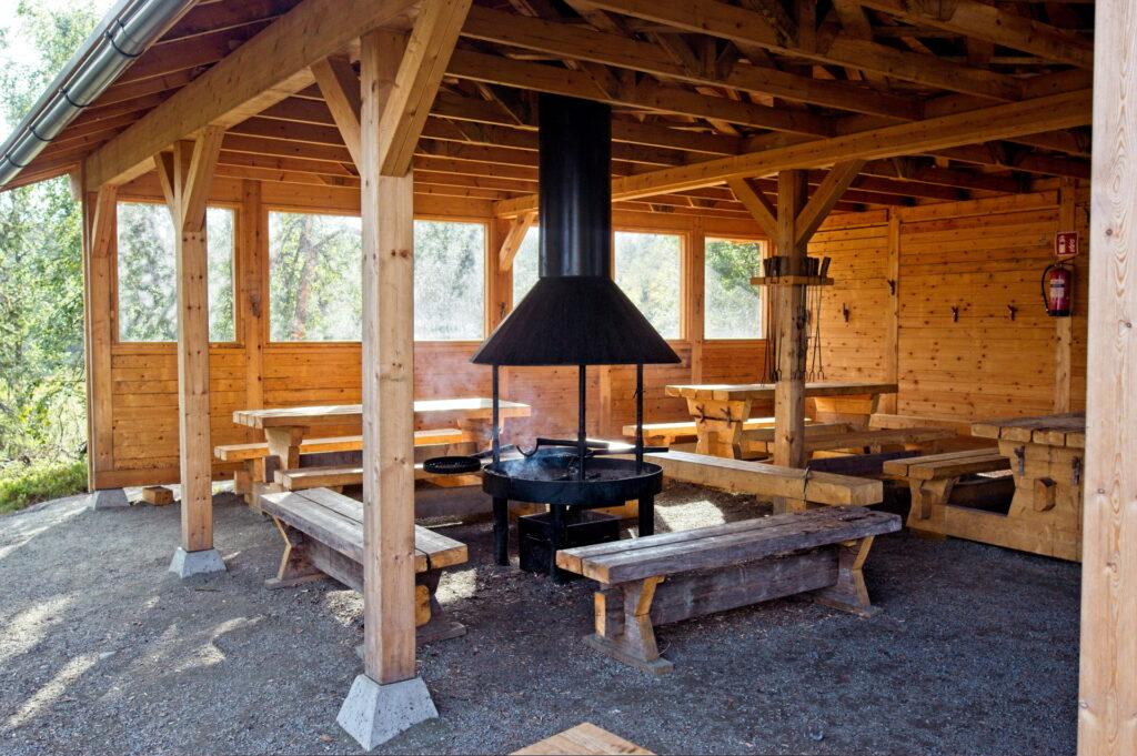 Katettu grillikota on moderni ja hyvin varusteltu, iso tulipaikka, penkkejä ja makkaratikkuja